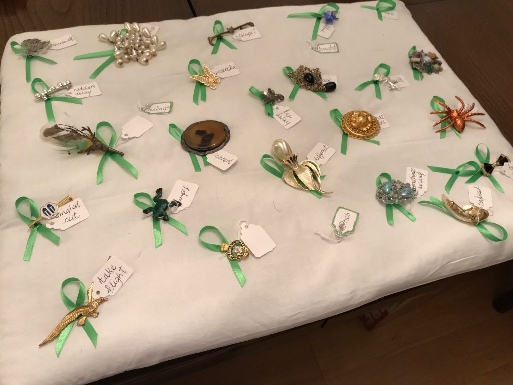 Photo of different brooches relating to mental health. These are defined as: Unusual, hidden away, hard to miss, escape, blue, alone, attention needed, guilt, black days, unsettled, damaged, scared, far away, black days, frightened, all that glitters, different, singled out, take flight, jumpy, PTS, some things missing, confused and bow out.